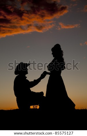 A cowboy couple is silhouetted in the sunset as if he were proposing.