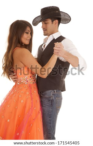 a cowboy dancing around with his beautiful woman in her dress. - stock photo