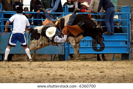 A cowboy Falling from a large bull - stock photo