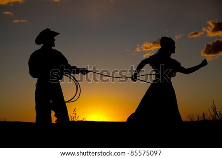 A cowboy has caught a woman with a rope in the sunset. - stock photo