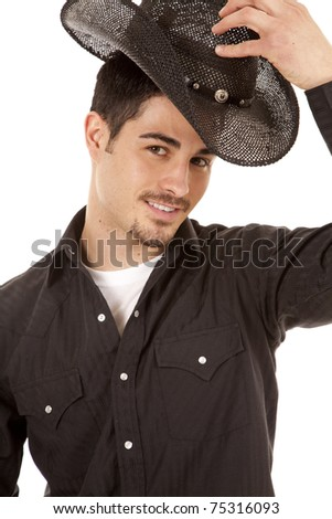 A cowboy has his hand on his black hat and is smiling.