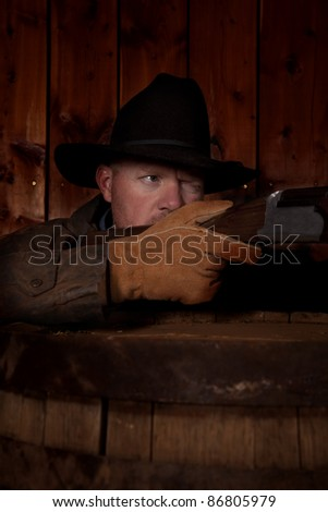 A cowboy hiding behind a barrel getting ready to shoot his rifle.