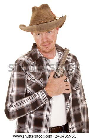 A cowboy holding his gun by his chest looking.