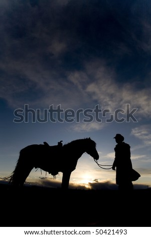 A cowboy holding his horse in the sunset - stock photo