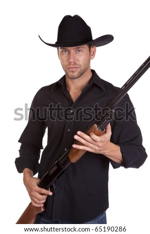a cowboy holding his rifle in his hands with a serious expression on his face. - stock photo