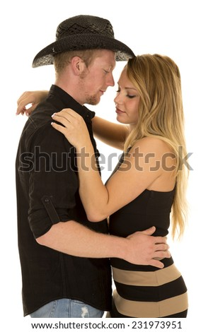 a cowboy holding on to his woman close looking at her. - stock photo