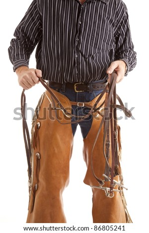 A cowboy holding on to the reins of his horse in his hands. - stock photo
