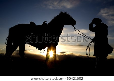 A cowboy holding onto his hat and his horse