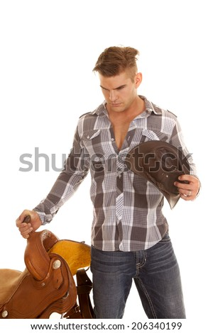 A cowboy holding onto his  saddle with a serious expression. - stock photo