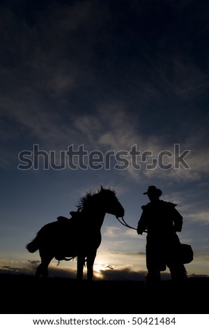 A cowboy holding the reigns of his horse in the sunset - stock photo