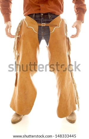 A cowboy in chaps standing with his hands ready. - stock photo