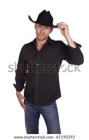 A cowboy in his black shirt and hat showing his small smile and touching his hat. - stock photo