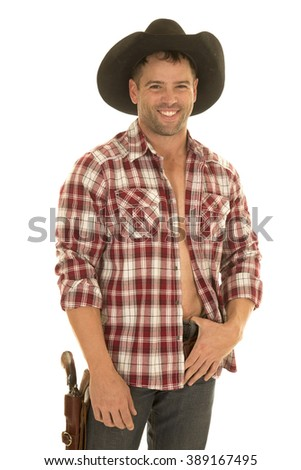 a cowboy in his plaid shirt with a smile, wearing his western hat with a pistol on his hip. - stock photo