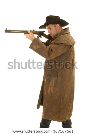 A cowboy in his western duster holding on to his rifle ready to shoot. - stock photo