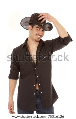 A cowboy is dressed in black holding his hand on his hat. - stock photo