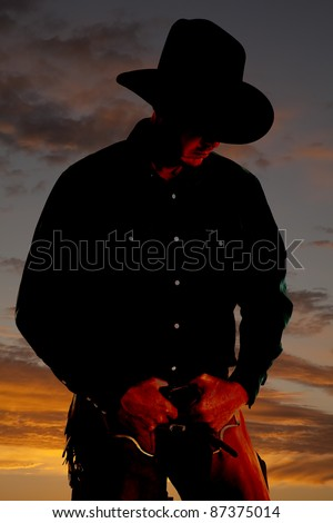 A cowboy is highlighted in the sunset and is looking down. - stock photo