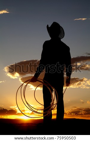A cowboy is holding a rope in the sunset. - stock photo