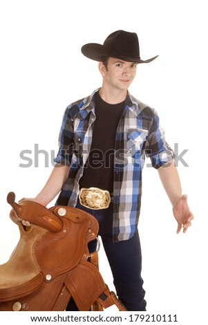A cowboy is holding a saddle in his hand looking.