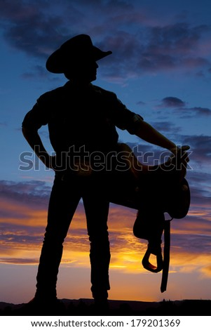 A cowboy is holding a saddle on his hip in the sunset. - stock photo