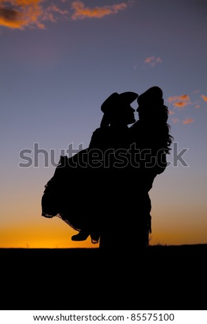 A cowboy is holding a woman in the sunset.