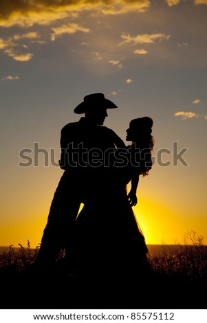 A cowboy is holding a woman in the sunset and dipping her. - stock photo