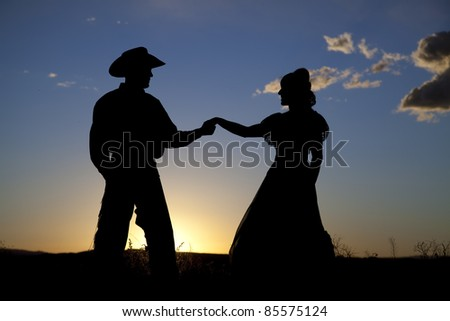 A cowboy is holding hands with a woman in the sunset.