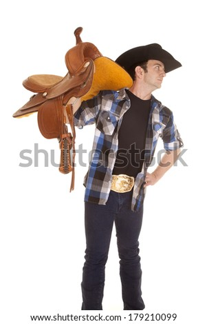 A cowboy is holding his saddle on his shoulder. - stock photo