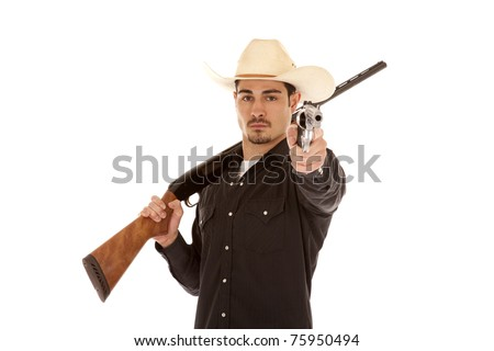 A cowboy is holding two guns.  A shotgun over his shoulder and a pistol pointing in his other hand. - stock photo