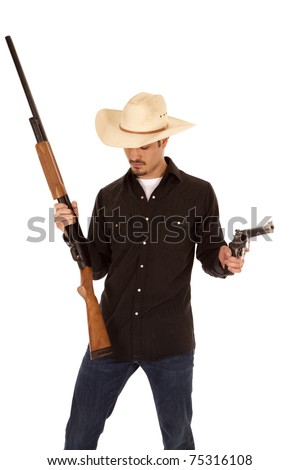 A cowboy is holding two guns and looking down. - stock photo