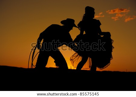 A cowboy is in the sunset playing flirty with a woman. - stock photo