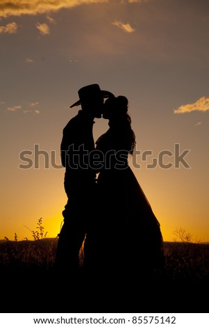A cowboy is kissing a woman in the sunset. - stock photo