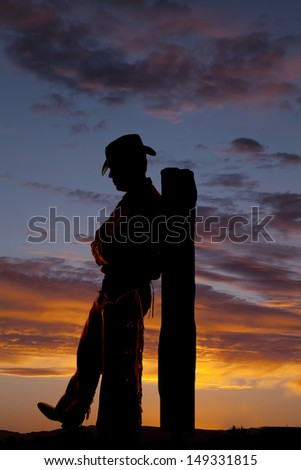 A cowboy is leaning back on a post.