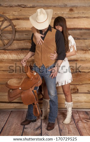 A cowboy is looking down while an Indian is looking over his shoulder. - stock photo