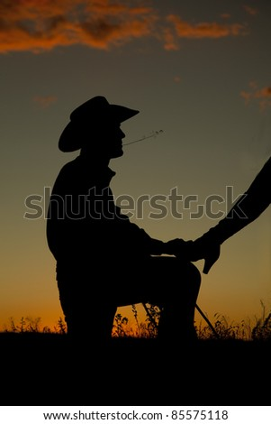 A cowboy is on his knee with a womans leg on him in the sunset. - stock photo