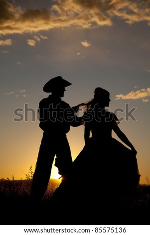 A cowboy is playing with a woman's hair in the sunset. - stock photo