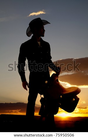 A cowboy is silhouetted in the sunset holding a saddle. - stock photo