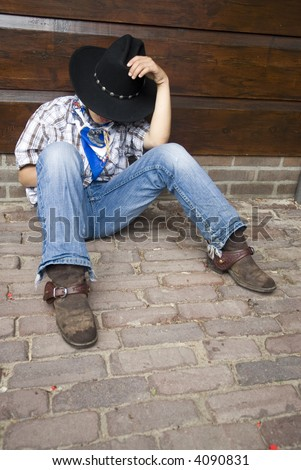 A cowboy is sitting and sleeping - stock photo