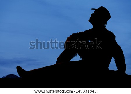 A cowboy is sitting in the evening looking up. - stock photo