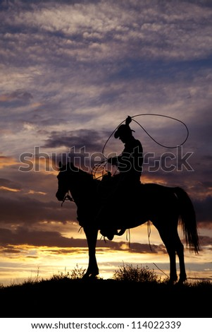A cowboy is sitting on a horse in the sunset swinging a rope.