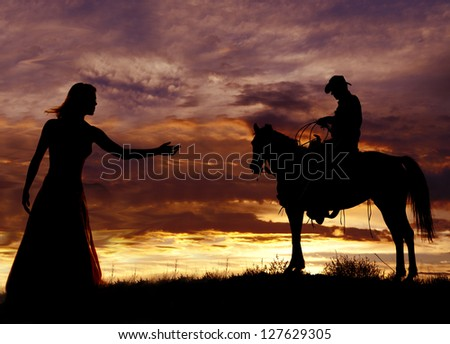 A cowboy is sitting on a horse in the sunset swinging a rope. - stock photo