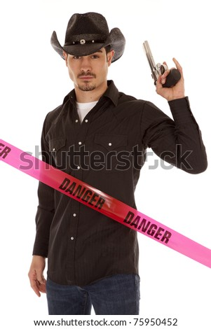 A cowboy is standing by a danger sign with a gun. - stock photo