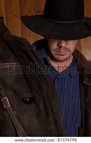 A cowboy is standing by a horse looking down - stock photo