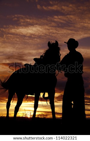 A cowboy is standing by his horse in the sunset.