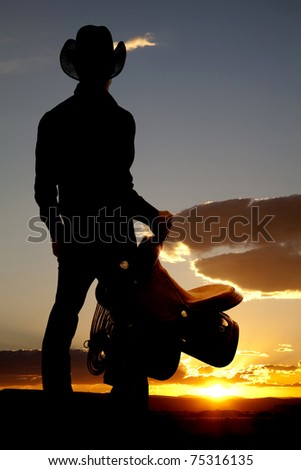 A cowboy is standing in the sunset holding a saddle.