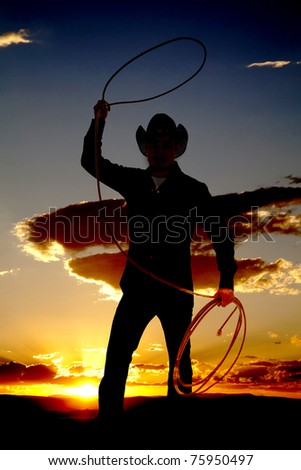 A cowboy is standing in the sunset twirling a rope - stock photo