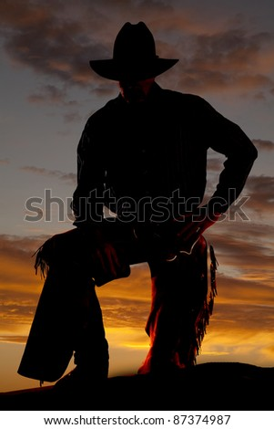 A cowboy is standing in the sunset with a leg up.