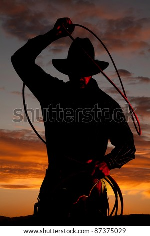 A cowboy is standing in the sunset with a rope.