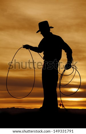 A cowboy is standing in the sunset with a rope in his hands. - stock photo
