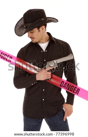 A cowboy is standing with a revolver by a danger sign. - stock photo