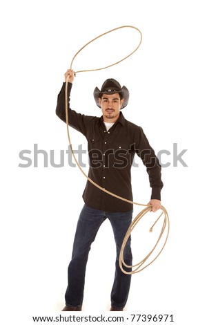 A cowboy is standing with a rope in his hand. - stock photo